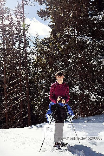 Jugendliches Mädchen beim Schneeschuhwandern im verschneiten Bergwald  Porträt  Steiermark  Tirol  Österreich