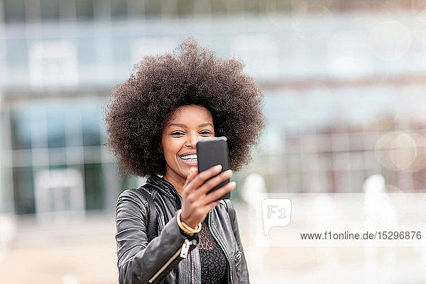 Junge Frau mit Afro-Haaren nimmt Smartphone-Selfie in der Stadthalle