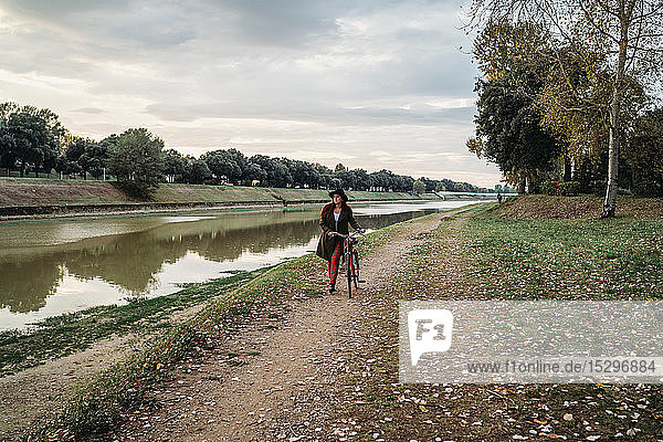 Young woman with long red hair pushing bicycle on riverside  full length  Florence  Tuscany  Italy