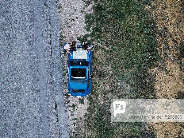Draufsicht von Freunden  die am Straßenrand die Straßenkarte auf der Motorhaube des Autos lesen