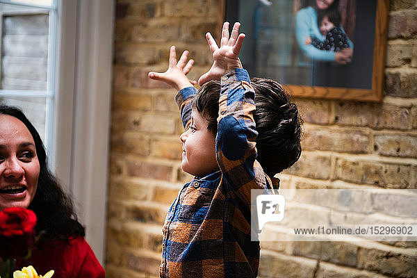 Männliches Kleinkind mit erhobenen Händen schaut die Mutter an und feiert den Muttertag