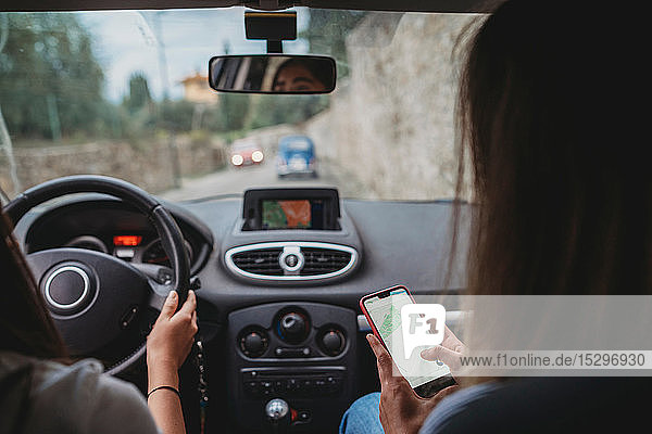 Friends using smartphone inside car