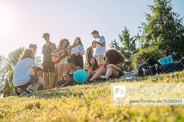 Gruppe von Freunden entspannt sich  spielt Gitarre beim Picknick im Park
