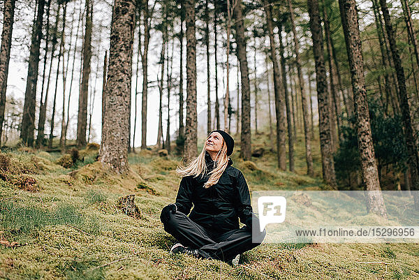 Trekker sitting cross-legged in forest  Trossachs National Park  Canada