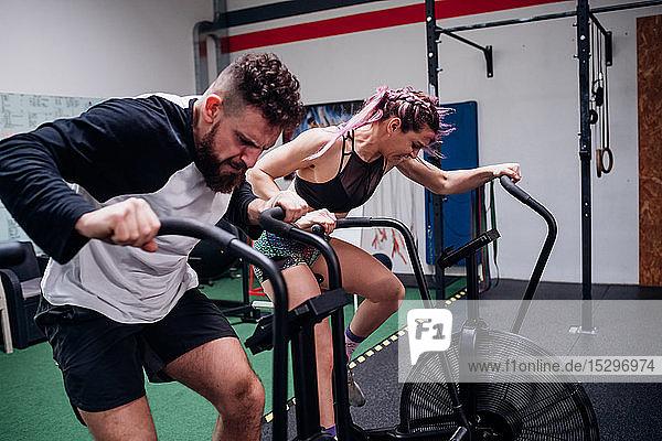 Junge Frau und Mann trainieren gemeinsam auf Turnhallen-Heimtrainern  Action