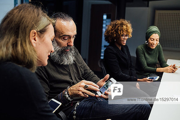 Business partners using smartphone at meeting in office
