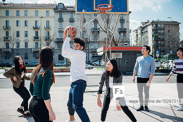 Young female and male adult friends playing basketball on city court