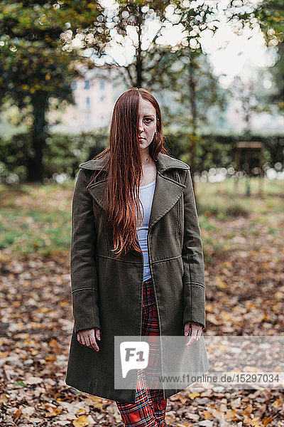 Young woman with long red hair in autumn park  portrait