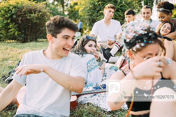 Gruppe von Freunden beobachtet Mann beim Picknick im Park  der mit Konfetti spielt
