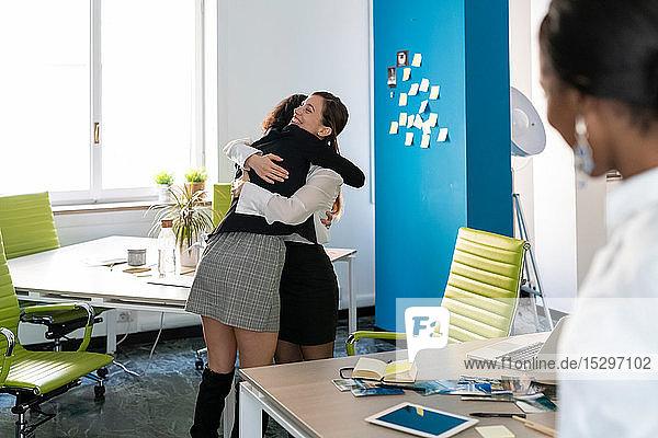 Zwei weibliche Geschäftskreative umarmen sich im Büro  Blick über die Schulter
