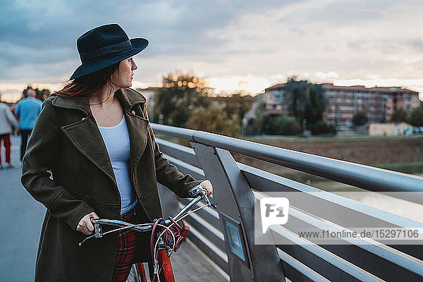 Young woman with bicycle looking out from footbridge at dusk  Florence  Tuscany  Italy