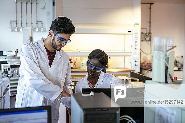 Junge männliche und weibliche Wissenschaftler betrachten Ergebnisse im Labor  geschnitten