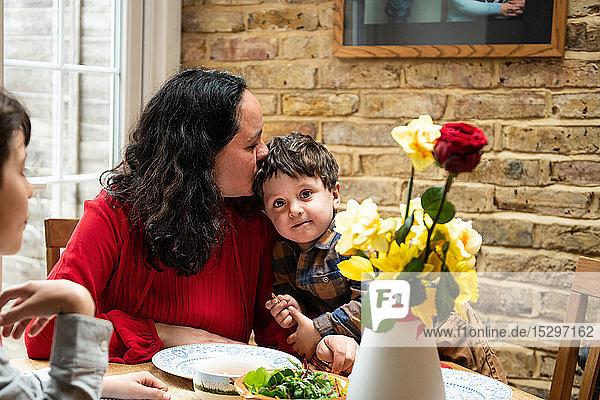 Junge mit Mutter und kleinkindlichem Bruder bei Tisch zur Feier des Muttertags