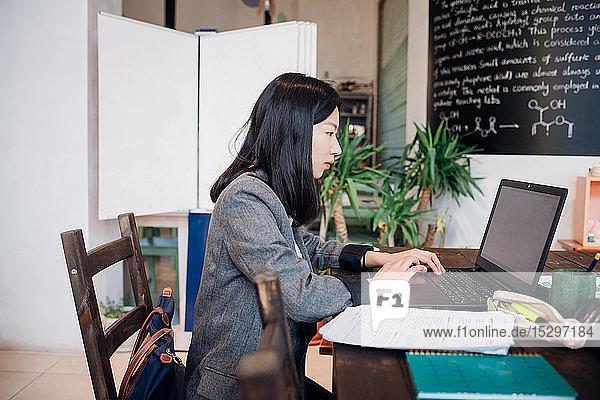 Junge Geschäftsfrau arbeitet ferngesteuert am Laptop am Cafétisch