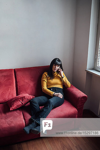 Woman talking on smartphone on sofa