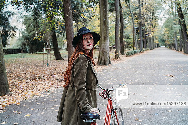Young woman with long red hair looking over her shoulder while pushing bicycle in autumn park  Florence  Tuscany  Italy