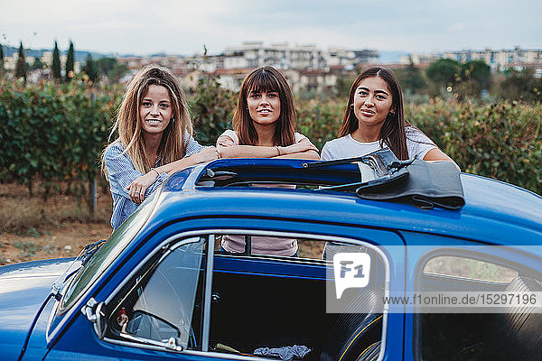 Friends posing beside car in countryside  Florence  Toscana  Italy