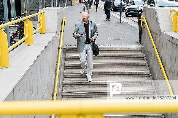 Geschäftsmann mit Smartphone geht eine Treppe hinunter  Mailand  Lombardei  Italien