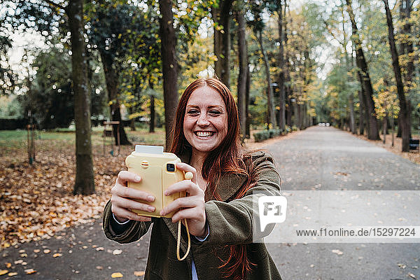 Young woman with long red hair taking instant selfie in autumn park