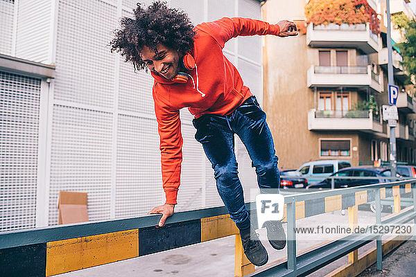 Junger Mann springt auf Bürgersteig über Trennwand  Mailand  Lombardei  Italien