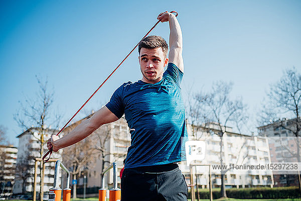 Calisthenics at outdoor gym  young man stretching resistance band