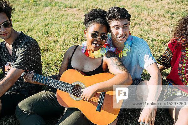 Freunde entspannen sich  spielen Gitarre im Park