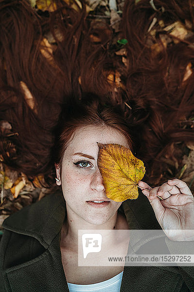 Young woman with long red hair lying amongst autumn leaves and covering eye with autumn leaf  overhead portrait