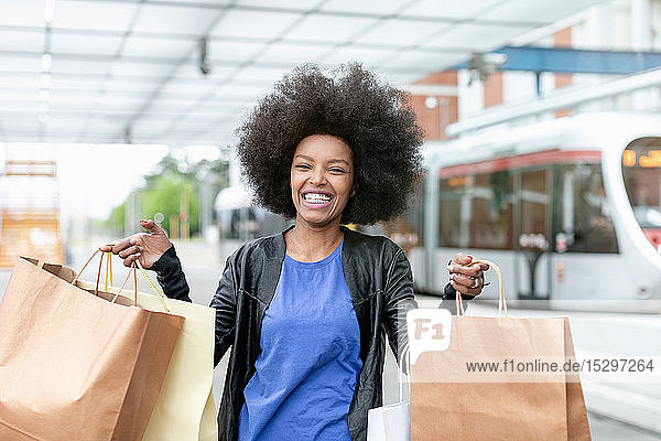 Young woman with afro hair at city train station holding up shopping bags  portrait