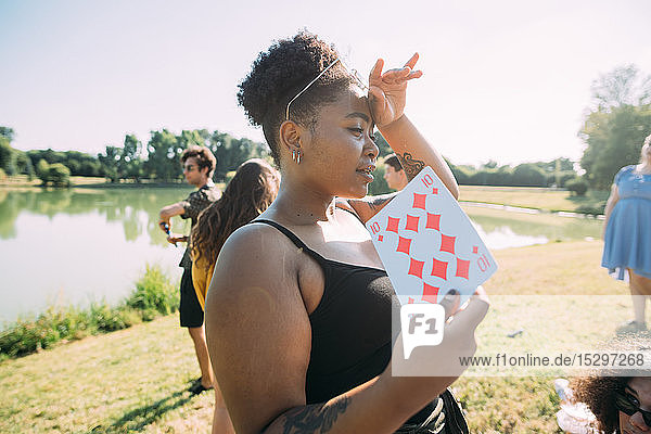 Young woman cooling off with playing card in park