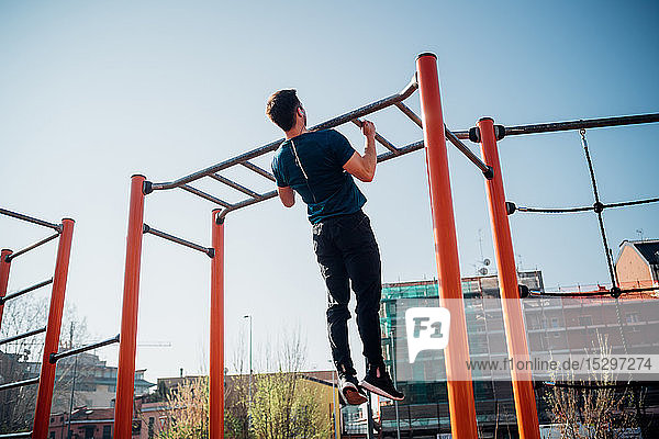 Calisthenics at outdoor gym  young man doing pull ups on exercise equipment  rear view