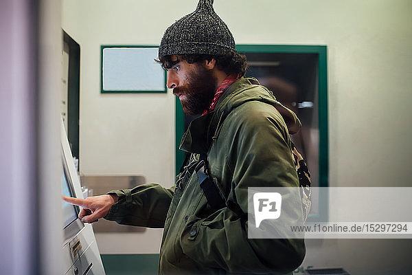Bearded young man using cash machine