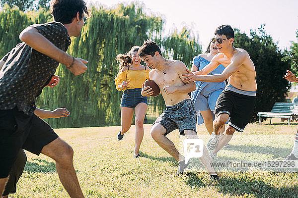 Gruppe von Freunden spielt Fussball im Park