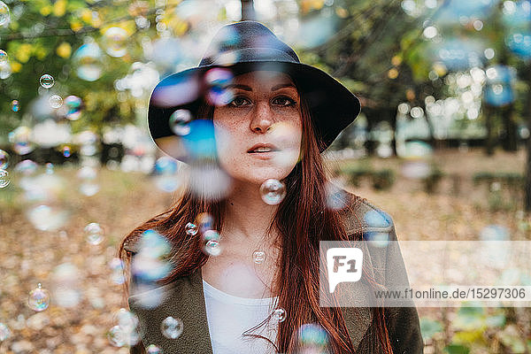 Young woman with long red hair amongst floating bubbles in autumn park  shallow focus portrait