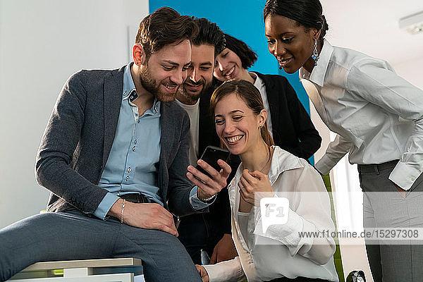 Junges weibliches und männliches kreatives Geschäftsteam betrachtet Smartphone im Büro