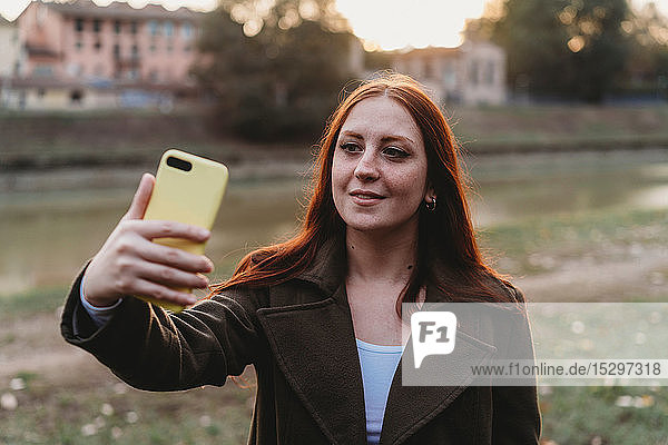 Young woman with long red hair taking smartphone selfie on riverside at dusk  Florence  Tuscany  Italy