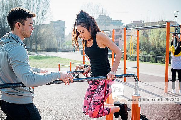 Gymnastik im Fitnessstudio im Freien  Trainer beobachtet junge Frau am Barren