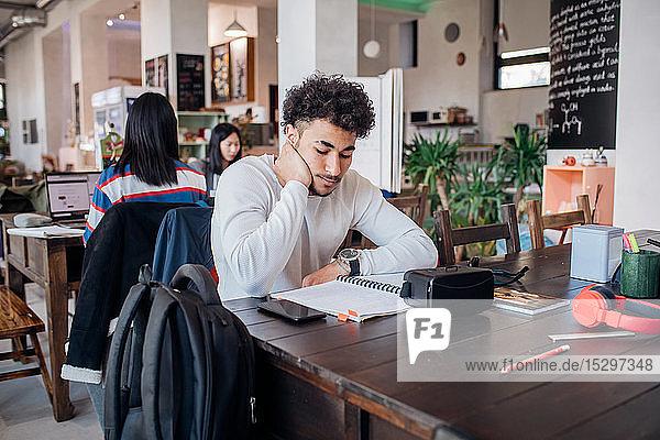 Junger Geschäftsmann arbeitet ferngesteuert am Laptop am Cafétisch