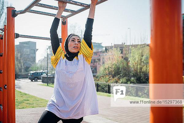 Calisthenics-Unterricht im Fitnessstudio im Freien  junge Frau hängt an Übungsgeräten