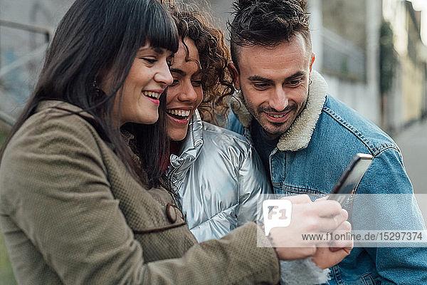 Freunde benutzen Smartphone auf dem Bürgersteig