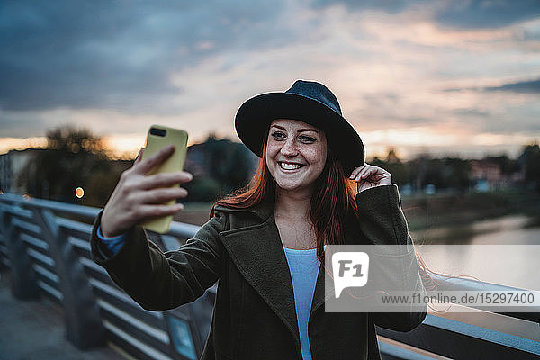 Young woman with long red hair on footbridge taking smartphone selfie at dusk  Florence  Tuscany  Italy