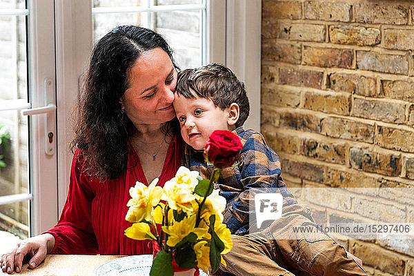 Männliches Kleinkind lehnt an der Schulter der Mutter und feiert Muttertag