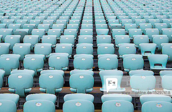 Rows of blue seats at empty open air stadium