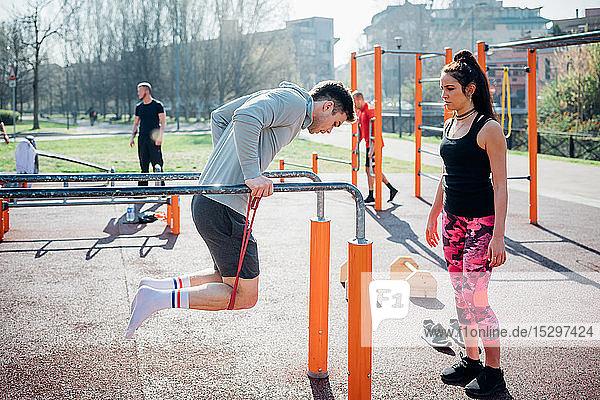 Gymnastik im Fitnessstudio im Freien  Trainer beobachtet jungen Mann am Barren