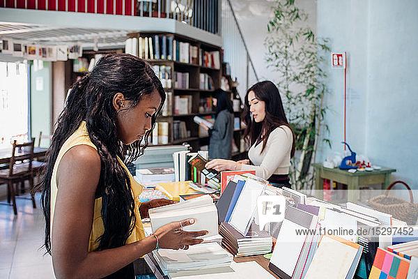 Junge Geschäftsfrauen stöbern in Büchern im Buchladen