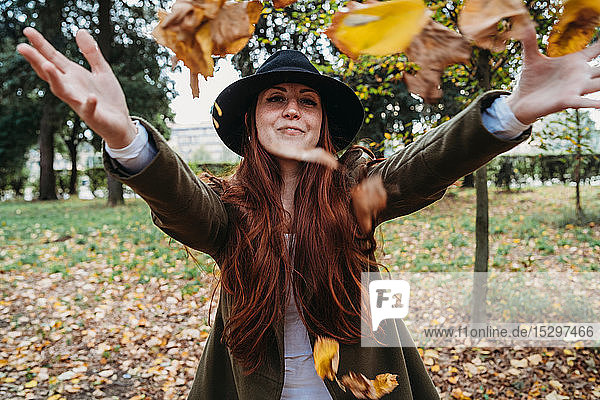 Young woman with long red hair throwing autumn leaves in park