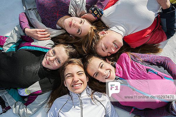 Fünf jugendliche Skifahrerinnen liegen im Kreis im Schnee  Portrait von oben  Tirol  Steiermark  Österreich