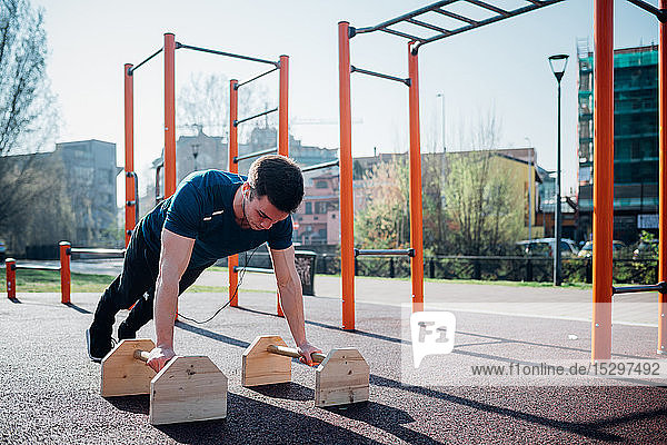 Calisthenics at outdoor gym  young man doing push ups on exercise equipment