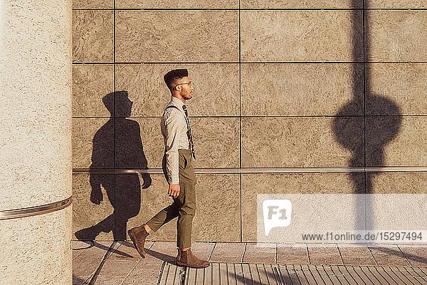Businessman walking past concrete wall  Milano  Lombardia  Italy