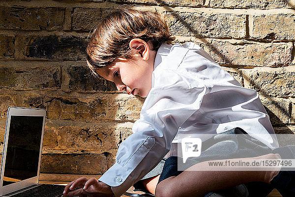 Junge in Schuluniform mit Laptop zu Hause