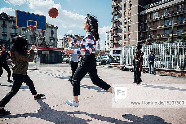 Junge weibliche und männliche erwachsene Freunde spielen Basketball auf dem städtischen Basketballfeld